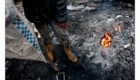 Chlapec se ohřívá u ohniště na skládce v Albánii