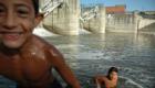 Romské děti si hrají v řece u splavu