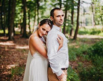 V lese nevěsta objímá ženicha