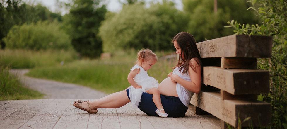 Maminka ukazuje dcerušce bříško